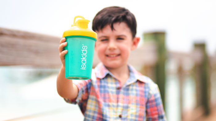 Young boy in a colorful plaid shirt holding up a yellow and teal IsaKids® shaker cup