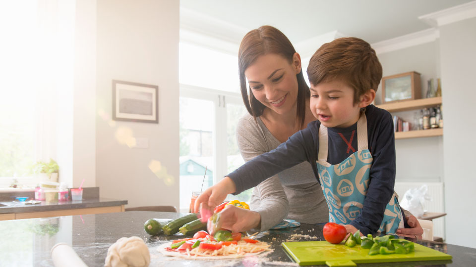 A mother making veggie pizza with her son in the kitchen
