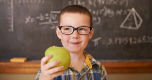 Boy with glasses holding apple