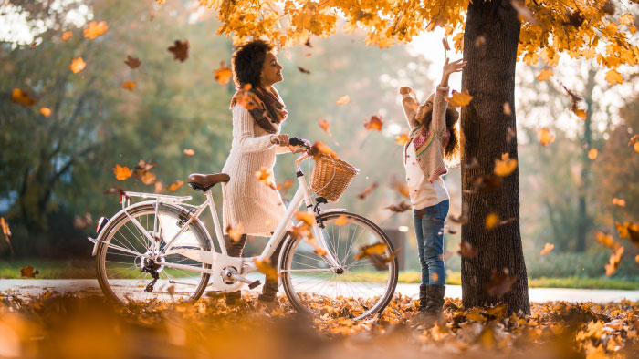 A woman walking her bike as autumn leaves fall