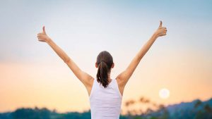 Woman holding two thumbs-up while looking at the sky
