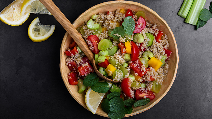 A wooden bowl of quinoa and fresh produce