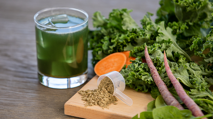 A glass of Organic Greens next to fresh vegetables