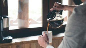 Someone pouring coffee into a mug