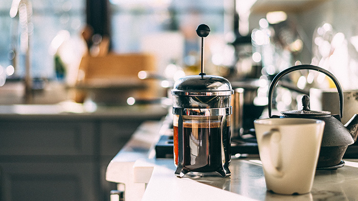 A French press filled with coffee and a mug on a counter
