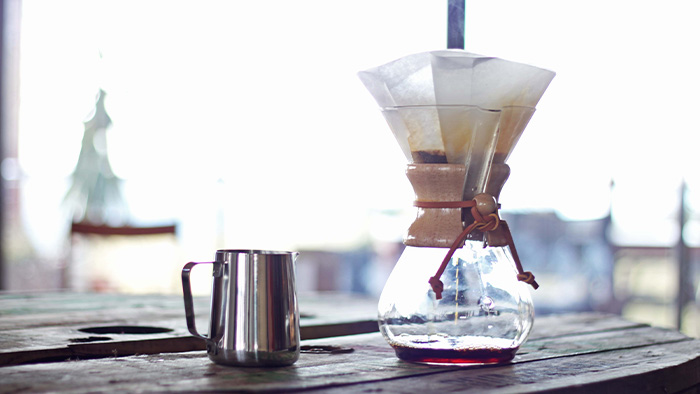 A chemex with a filter and a mug on a table