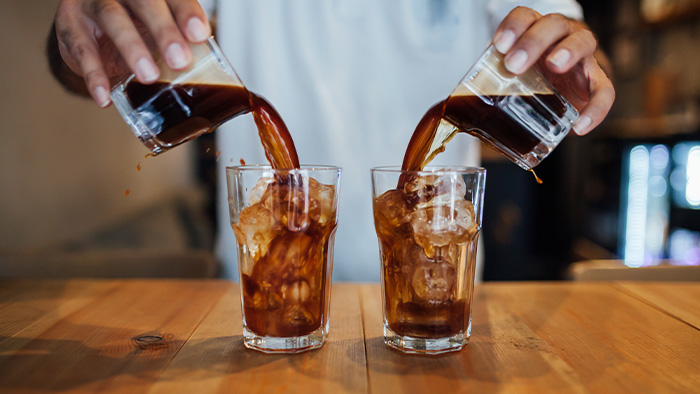 Someone pouring cold brew coffee into two glasses with ice