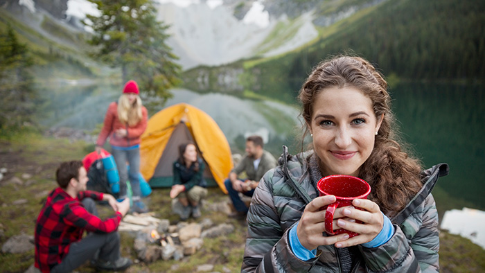 Woman holding mug while she and her friends camp by the lake
