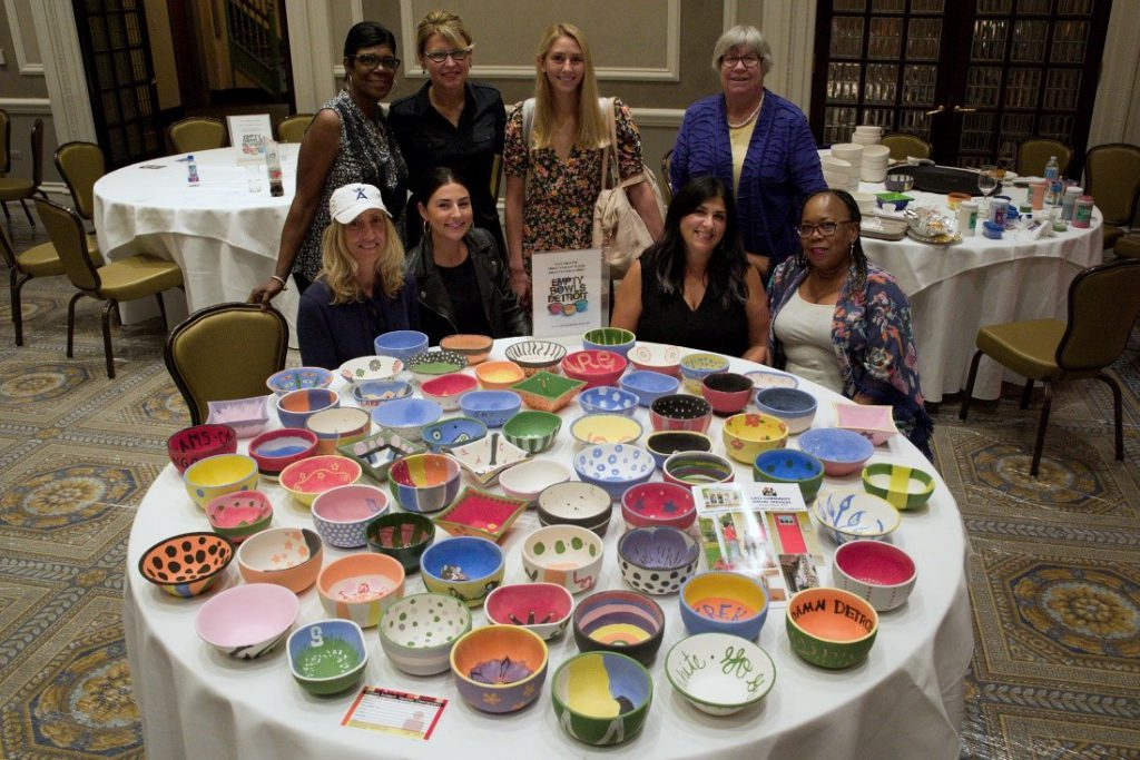 Women smiling behind empty colorful bowls