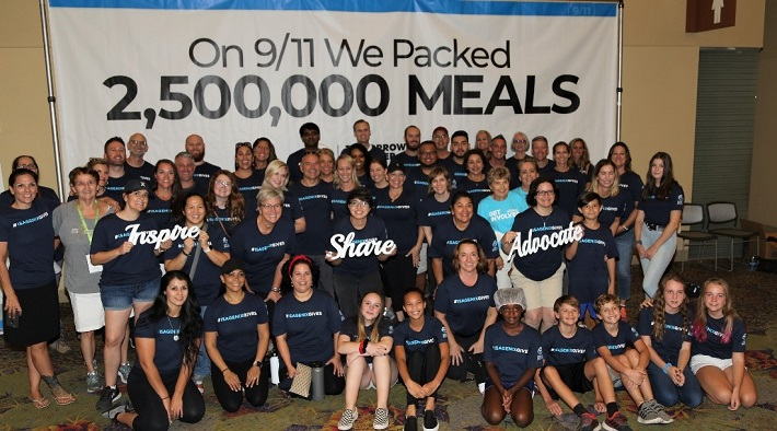 Isagenix corporate members and their families gather in a group photo after packing meals