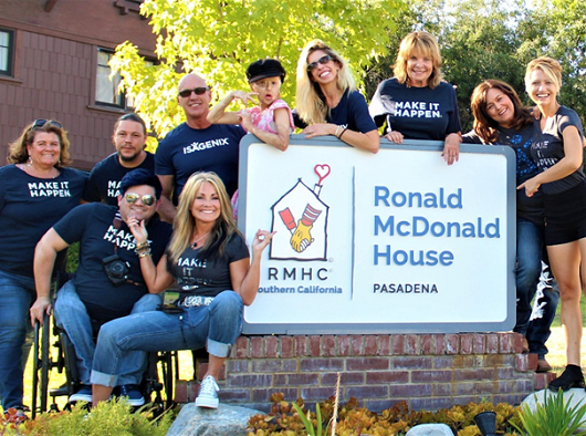 Isagenix Independent Associates smiling in front of Ronald McDonald House sign