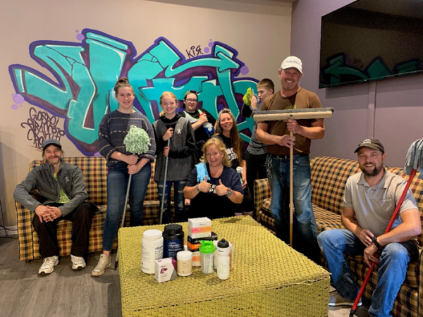 Men, women, and teenagers smiling while holding painting and cleaning supplies