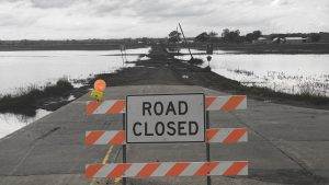 Sign that says Road Closed on traffic barrier on a road surrounded by water.