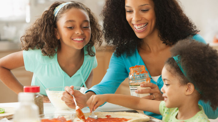 A mother and her daughters putting sauce on pizza