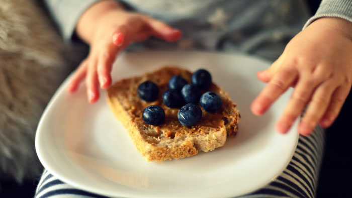 A plate of peanut butter toast with blueberries on top