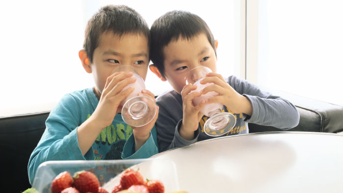 Two boys drinking strawberry smoothies from glasses
