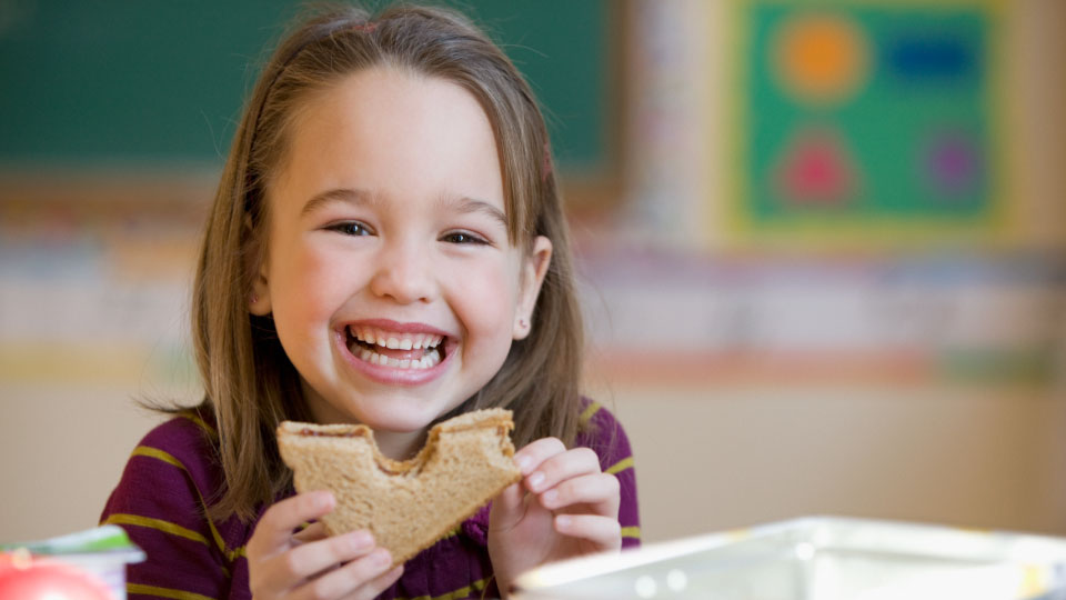 A little girl eating a peanut butter and jelly sandwich