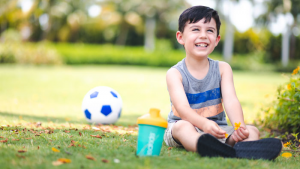 Young boy smiling and enjoying super smoothie after playing soccer