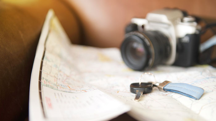 A camera and car key resting on a road trip map