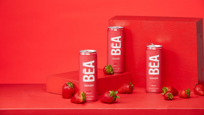 3 cans of Berry Bellini BĒA Sparkling Energy Drink against a red backdrop