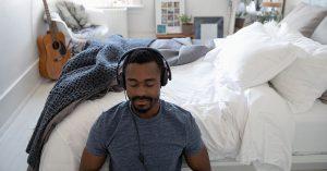 Man in bedroom wearing headphones