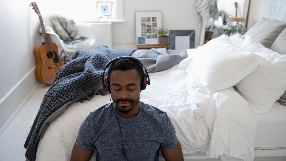 Man in bedroom wearing headphones