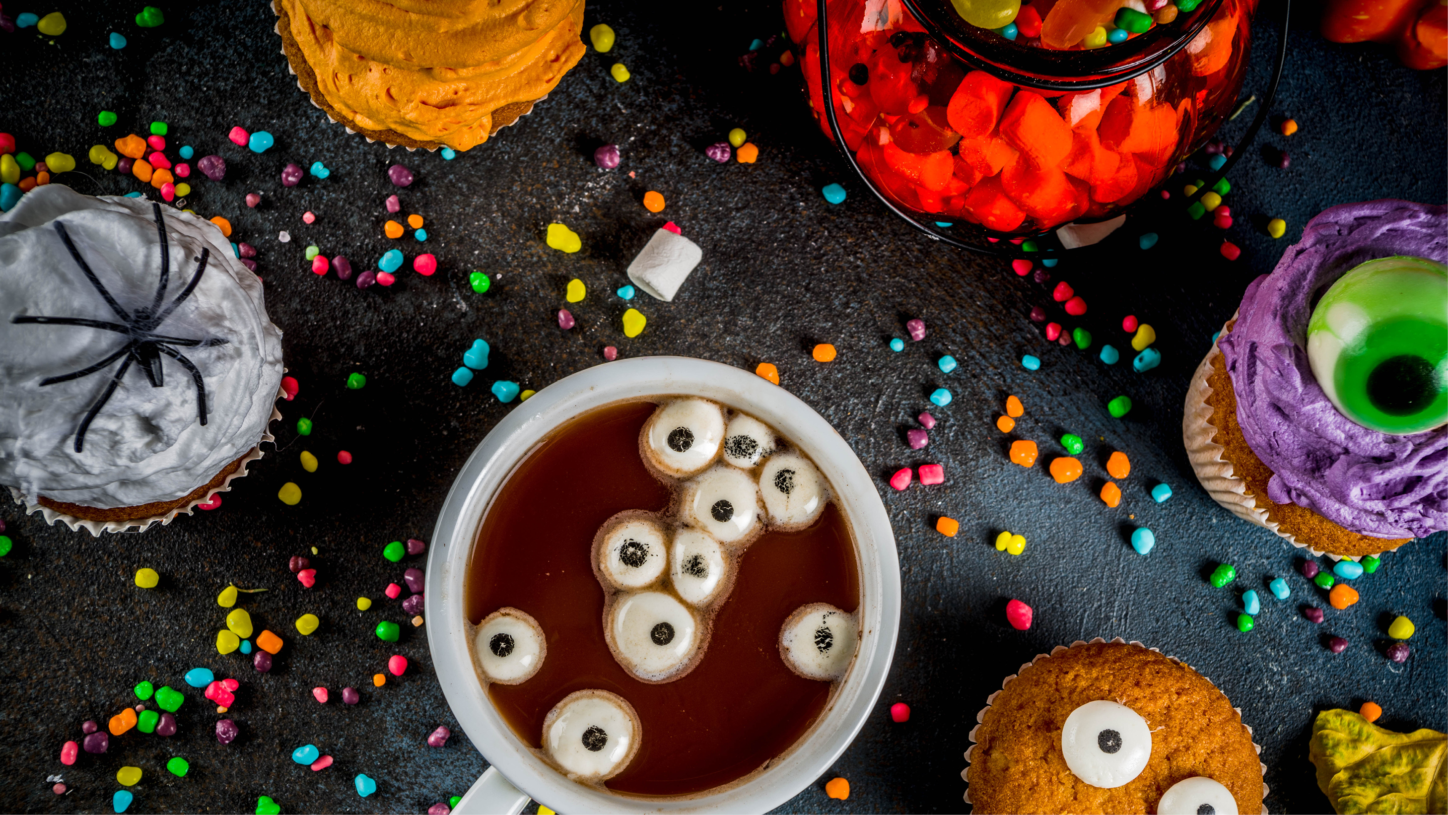 Table with bowls of Halloween candy and sprinkles