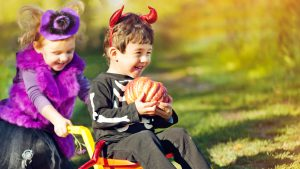 Two kids dressed up in costumes playing and holding a pumpkin