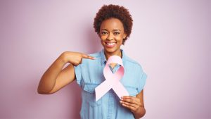 Woman pointing to a breast cancer awareness ribbon she's holding