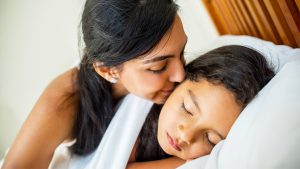 Mom kissing her daughter's cheek in bed
