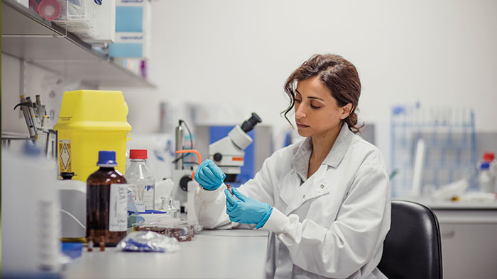 Woman in a lab testing a bottle.
