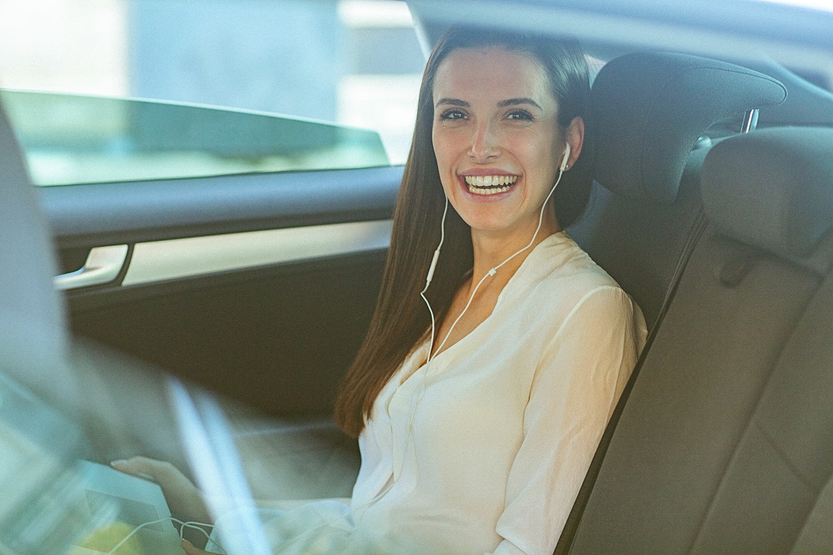A woman smiling and listening to earbuds in the car