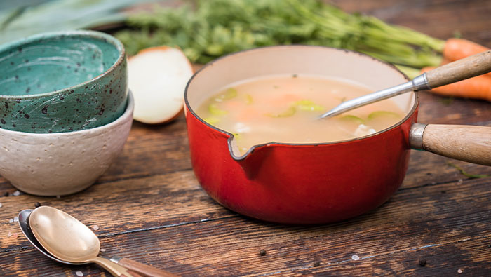 Saucepan with leftover turkey and vegetable soup with bowls and vegetables on the table