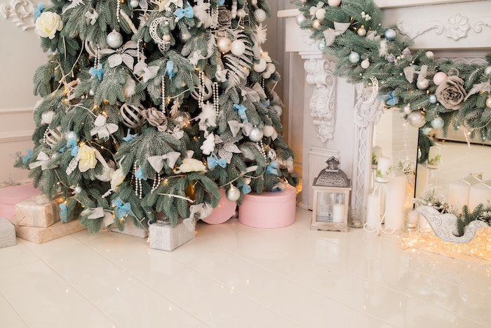 A corner Christmas tree with white and blue decorations