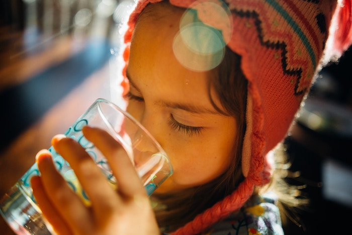 Girl drinking water out of a glass