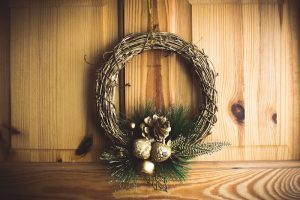 A wooden Christmas wreath with gold ornaments