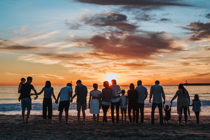 People holding hands on the beach as they watch a sunset