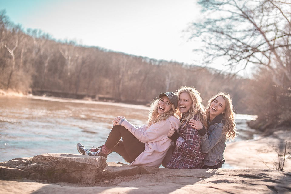Three friends posing for a picture outside