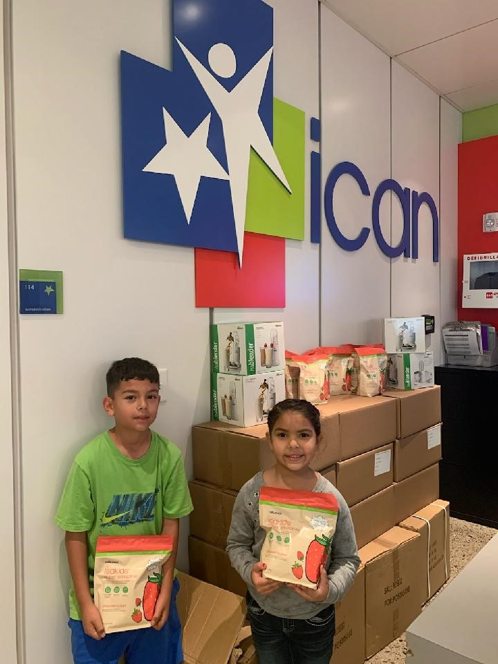 Children holding IsaKids Super Smoothie pouches at ican building
