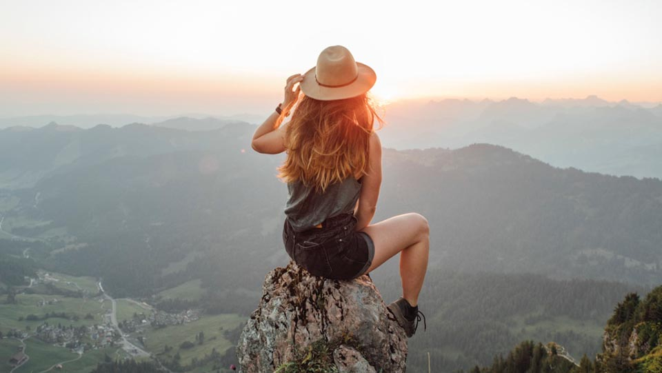 woman on top of mountain - cool hat