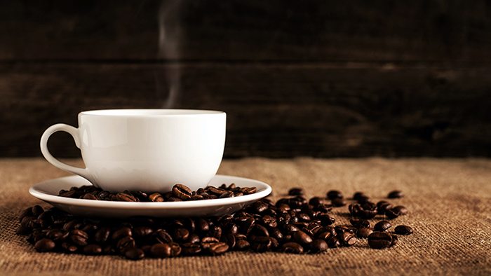 hot cup of coffee resting on coffee beans