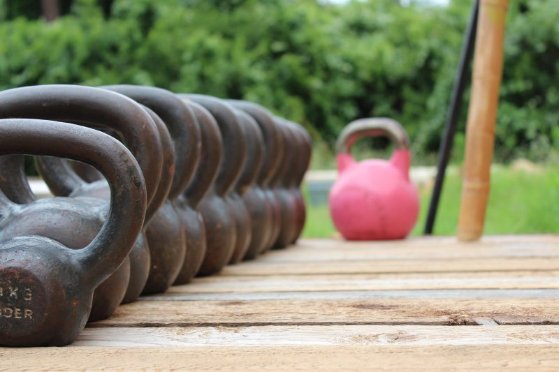 A row of black kettlebells and one pink kettlebell