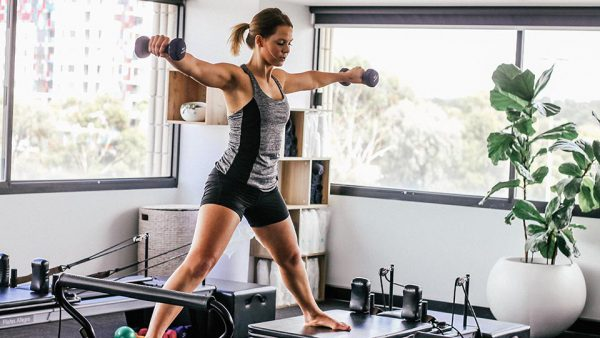 Woman working out at home with dumbbells