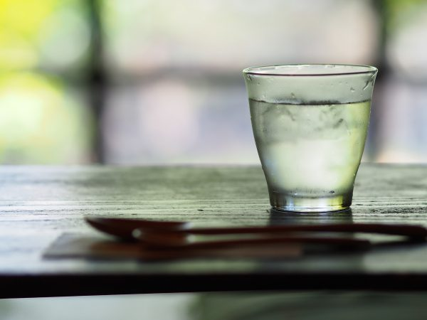 A glass of water on a wood table