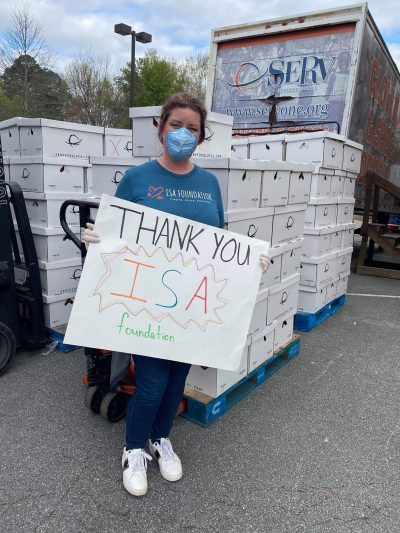 "A woman in a face mask holding a ""Thank You ISA Foundation"" sign"