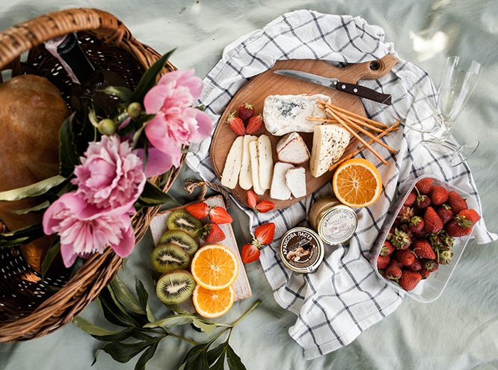 Charcuterie board with cheese, fruit, and flowers
