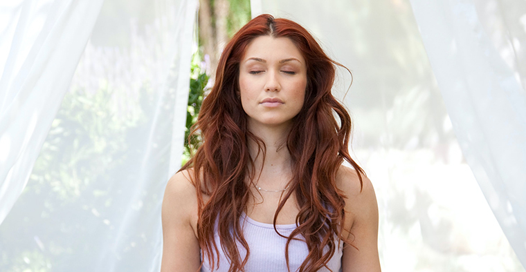 A woman meditating with her eyes closed