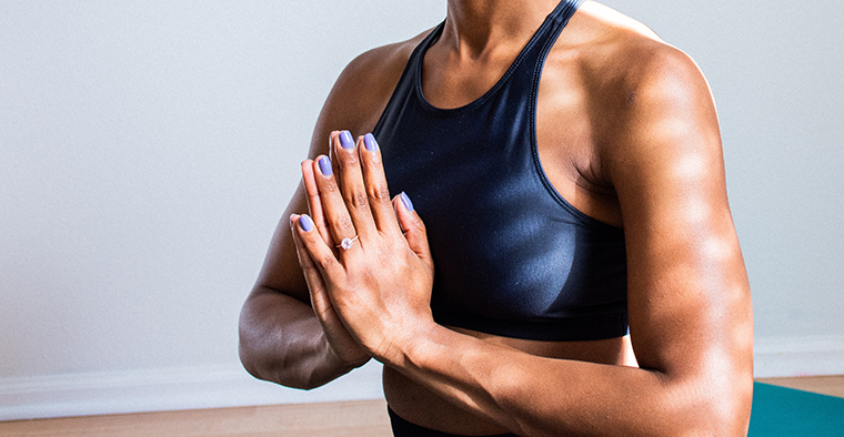 Close-up on a woman pressing her hands together during yoga