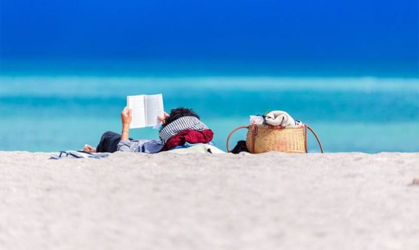 Person lying down at the beach and reading a book
