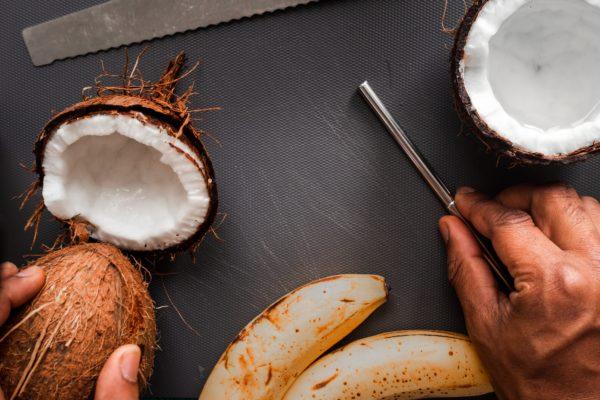 A man's hands preparing coconuts and bananas
